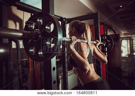 Young sexy blonde girl in the gym preparing to do squat