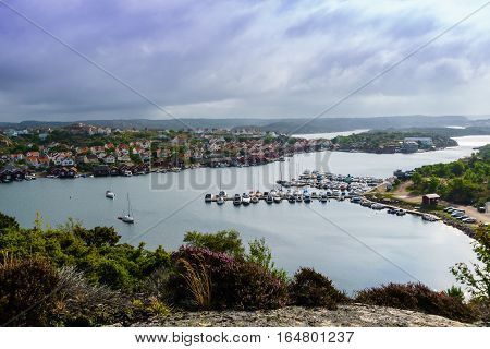outlook view over kungshamn by the sea picturing harbour and old fishing village boats cars and the sea between the viewer and the town.
