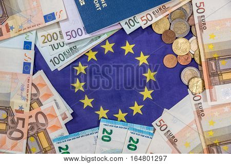 euro bills with coin passport above flag