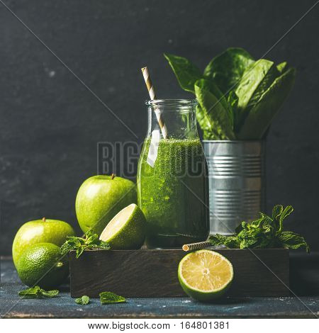 Green smoothie in glass bottle with apple, romaine lettuce, lime and mint, dark background, selective focus, square crop, Detox, dieting, clean eating, vegetarian, vegan, healthy lifestyle concept