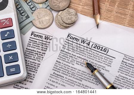 tax form w4 with pen and us dollar calculator and pen.
