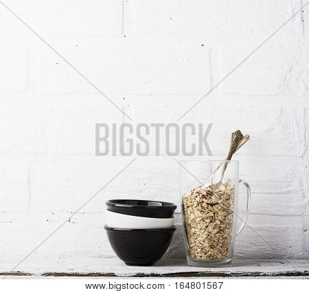 Simple kitchen still life with ceramic cups of contrast, a tall glass with oat flakes in one piece for the preparation of healthy wholesome breakfast comfort food on a background of a white brick wall.