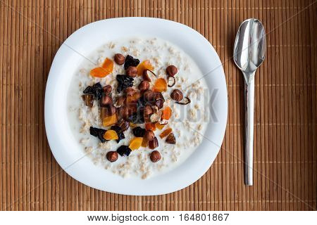 Bowl of homemade oatmeal porridge with dried apricots, hazelnuts, dates and dried plums  on bamboo napkin with spoon. Hot and healthy food for Breakfast.