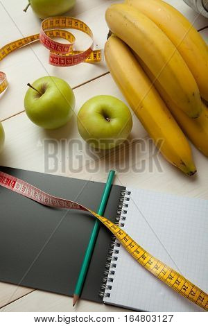 Diet, notebook, fruit with a measuring tape on a white wooden table