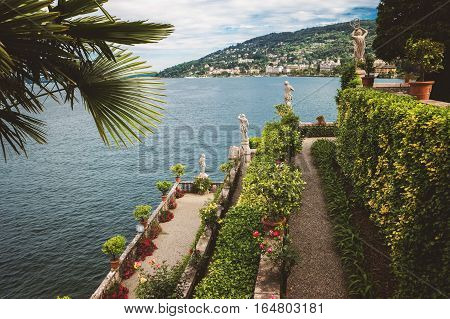 Green plants and statues. Buildings on green mountain. View from Isola Bella.