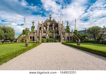 Green plants and old statues. Sculptures on sky background. Garden of Isola Bella.
