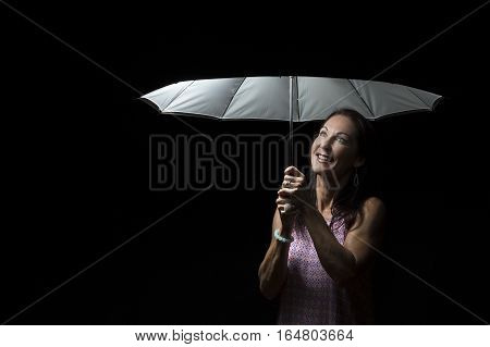 Beautiful woman with pink dress standing under an umbrella at night