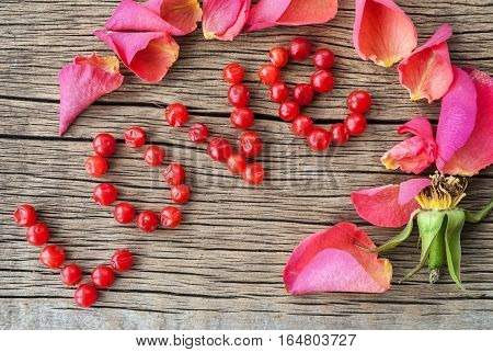 Valentine card concept. with love inscription made of red berry fruits, on wooden background.