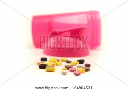 Few black, yellow, pink, purple, white pills and pink shaker