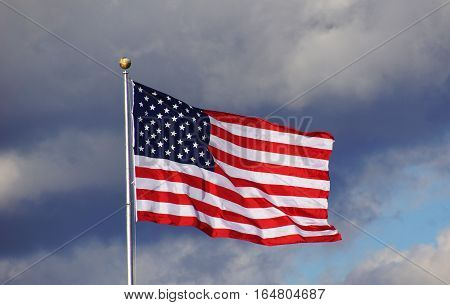 The American Flag on a background of a dark blue cloudy sky