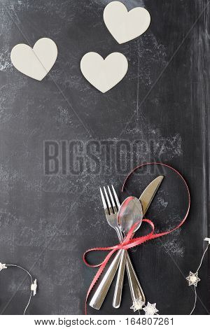 Top view of Valentines day dinner table setting with cutlery over a rustic blackboard background with wooden cut out hearts and fairy lights.