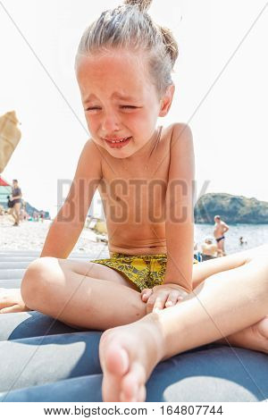 Little boy with dirty face is crying on the beach