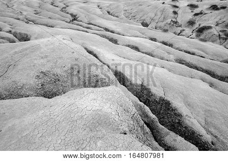 Black and white close-up with dried ground covered with cracks. Natural dry soil texture brown drought theme in rural arid area background for design.