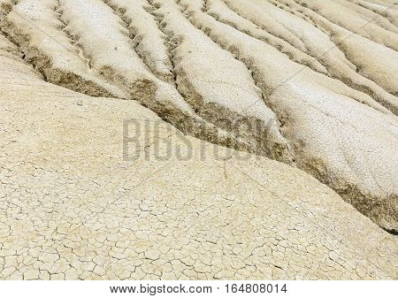 Vintage Close-up With Dried Ground Covered With Cracks. Dried Out Creek Bed Over Arid Area Of Sparse