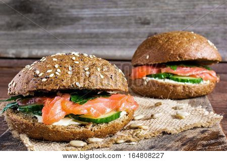two sandwiches with cereals bread and smoked salmon with herbs cucumbers and cheese on wooden background with copy space for healthy breakfast. close up. shallow depth of field