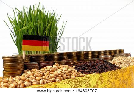 Germany Flag Waving With Stack Of Money Coins And Piles Of Wheat And Rice Seeds