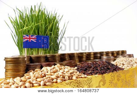 New Zealand Flag Waving With Stack Of Money Coins And Piles Of Wheat And Rice Seeds