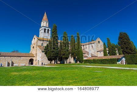 Aquileia - April 2016, Italy: Ancient Roman Сhurch in the city of Aquileia against the clear blue sky (Basilica di Santa Maria Assunta)