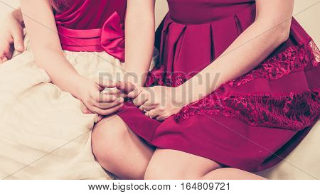 Elegance and style. Two fashionable elegant part body women sitting on sofa. Mother and daughter wearing dresses.
