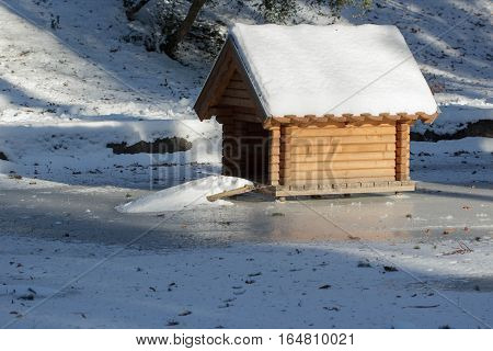 wooden shelter for wild animals covered with a layer of fresh snow