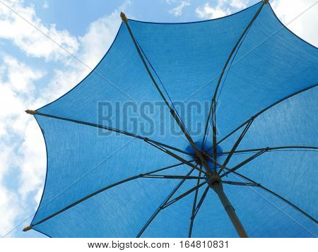 One vibrant blue colored sunshade against bright blue sky and white cloud