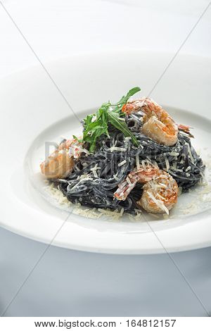Pasta with cuttlefish juice on a plate. With shrimps