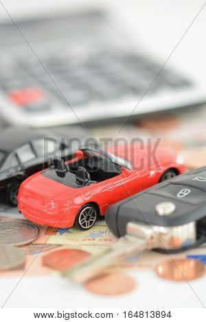 Renting or buying a car concept with toy cars, money and car key