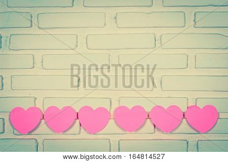 Pink sticky notes hearts shaped hearts lined holes on the wall. vintage style