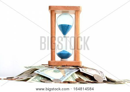Sand pouring on hourglass standing on pile of money, suggesting deadline concept