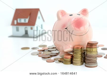 Savings for real estate project with small model house  and piggy bank climbing on piles of coins
