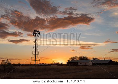 A water-pumping windmill at sunset on a farm near Ritchie in the Northern Cape Province of South Africa