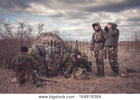 Hunters preparing for team hunting in rural field with hunting tent in overcast day