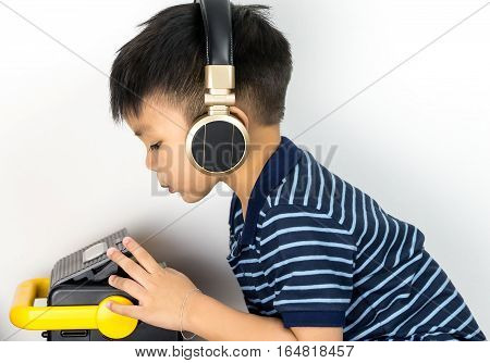 asian boy is listening to music through headphone with cassette tape player
