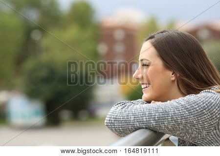 Side view portrait of a satisfied girl looking away leaning on a railing of a balcony with an urban background