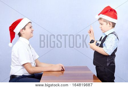 In Santa Claus caps two brothers are spending a photo session