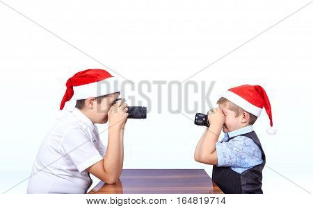 Two brothers in caps of Santa Claus are photographing of each other