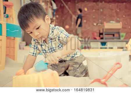 Asian boy is playing in educational Sandbox playground