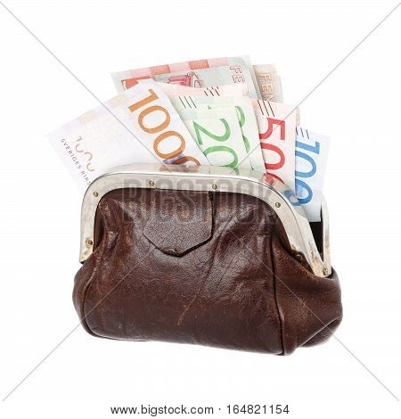 One brown purse filled with Swedish banknotes in the demoninations of 100 200 500 and 1000 krona isolated on white background.