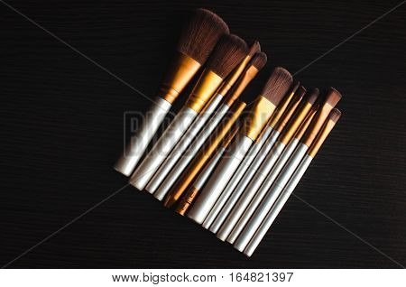 Makeup brushes on the table wenge dark were gold