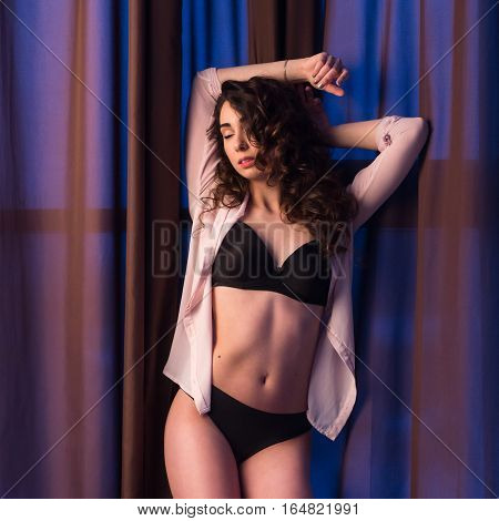 Beautiful languid girl with sexy figure in blue shirt, curly hair and perfect makeup, posing on a background of dark brown curtains, looking to camera, space for background. Bra light.