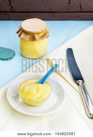 Vertical image of freshly made lemon curd in a glass dish showing homemade lemon curd in a jar on a blue wooden table room for copy space and text