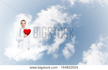 Young woman doctor against sky background holding red heart