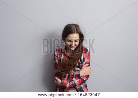 Girl Freezes From The Cold, Hugging Her Arms. Embarrassed And Looking At The Floor