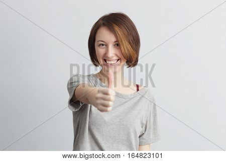 Red-haired girl with freckles showing a thumbs up approving the selection. Smiling from ear to ear.