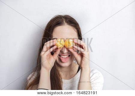 Girl with long hair fooling around closing her eyes with tangerines poster