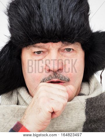 Elderly Man Suffering From A Cough. Bundled Up In Fur Hat And Warm Scarf.