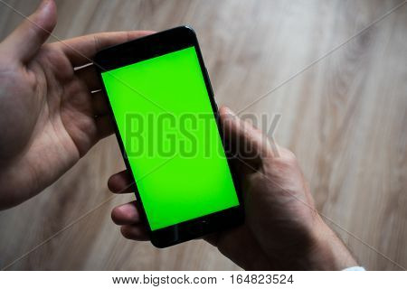 smartphone with green screen for key chroma screen. In the hands of a man .