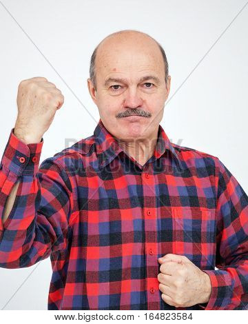 Elderly bald man with a mustache shows his hand with his fists. The call to action and a show of force.