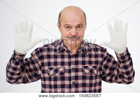 Elderly bald man with a mustache wearing cotton gloves and displays them. Protection of hands from calluses while working
