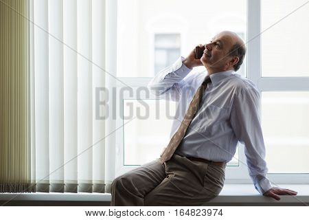 Elderly Man In A White Shirt And Tie Talking On The Phone. Important Talks During A Break At Work